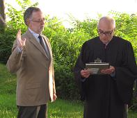 Justice Charles Brown swears in Peter Masterson as an Asharoken Village Trustee.
